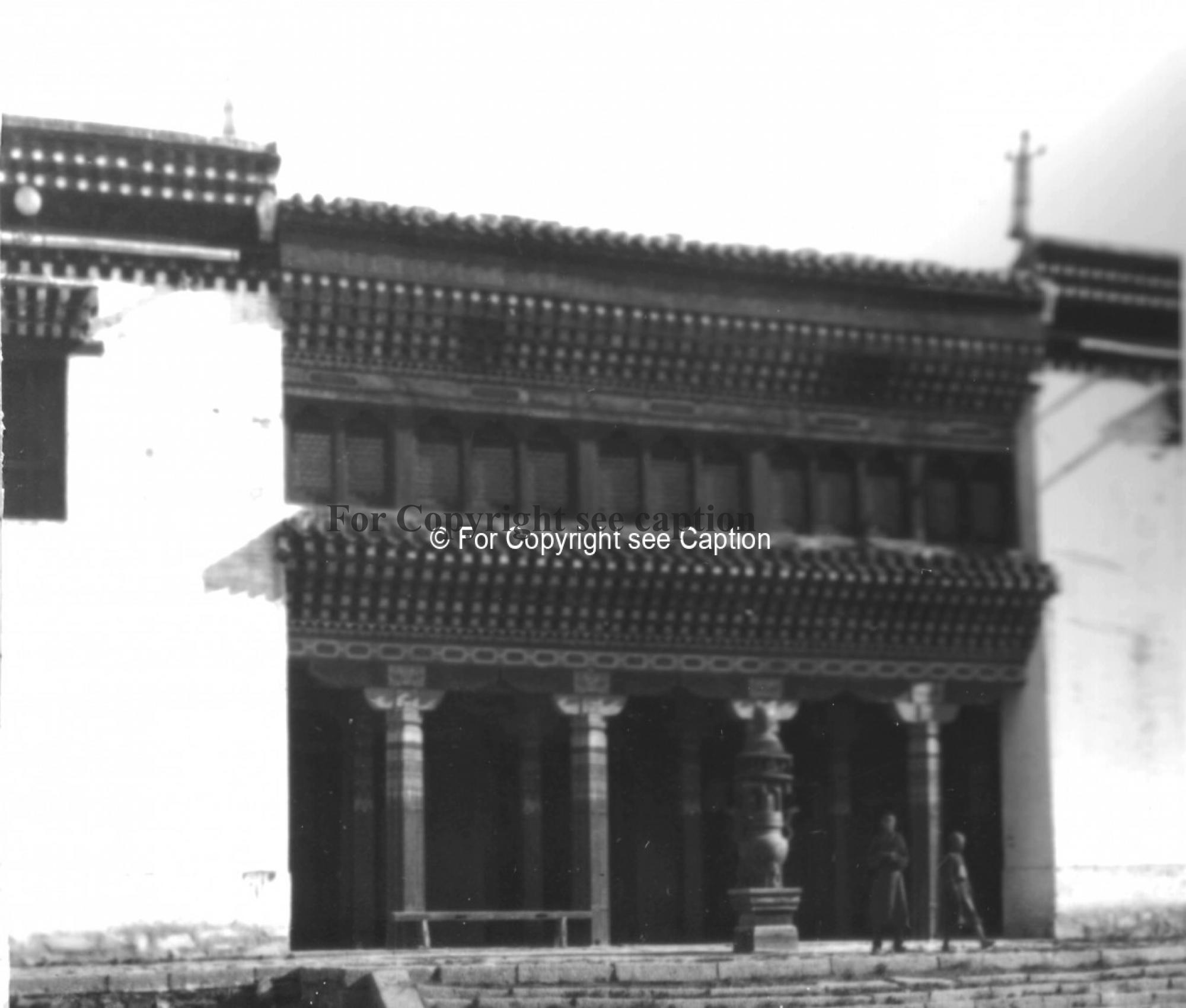 Entrance of the main assembly hall with an incense vessel and two novices. Film Archives ?